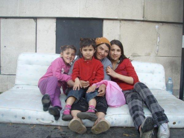 Mother and three children sitting on a mattress in Paris